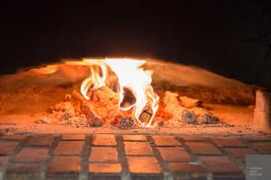 Eld i bakugn inför bakning av ljusugnsbröd.